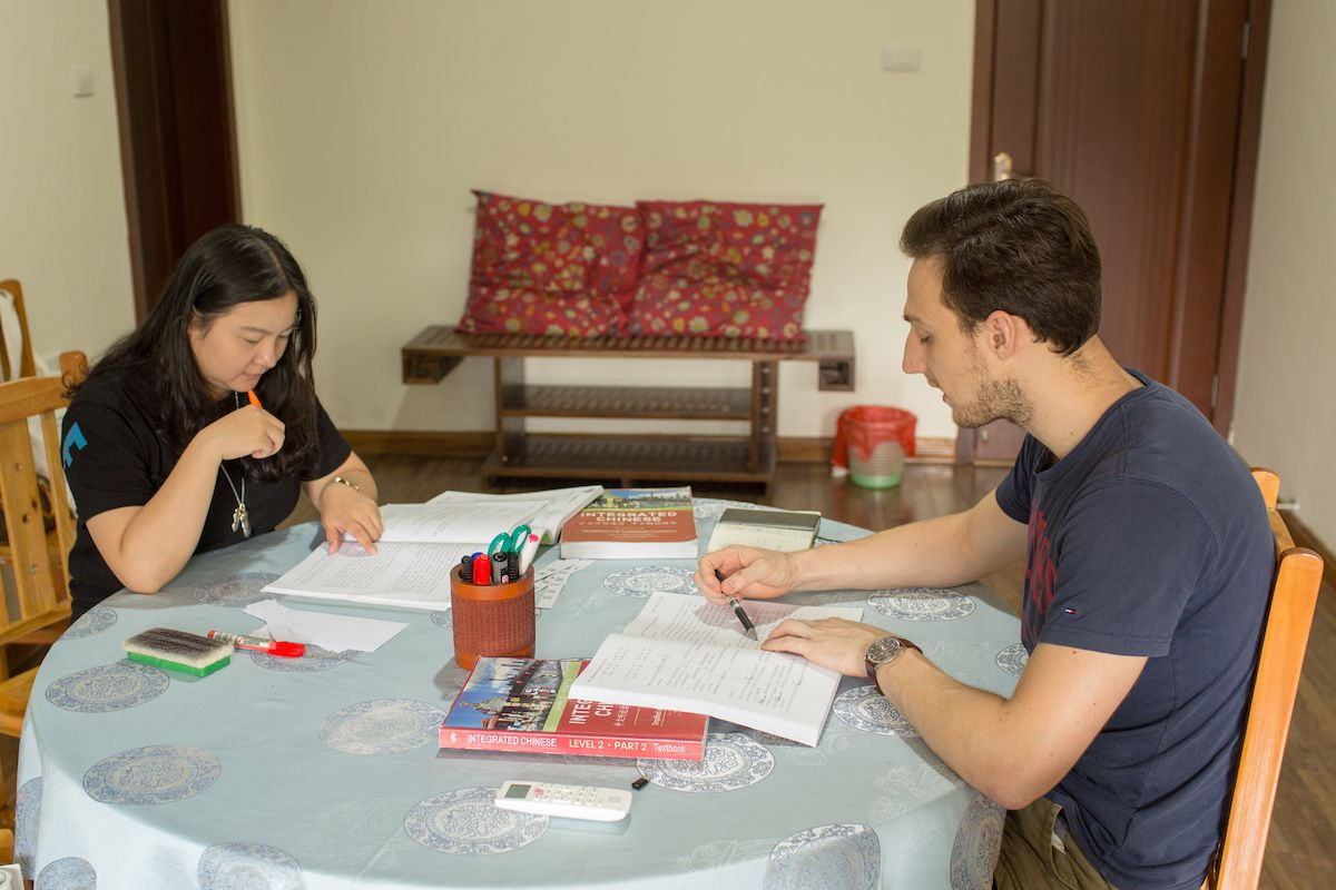 a western man and woman hold pens and look at textbooks while sitting at a circular table