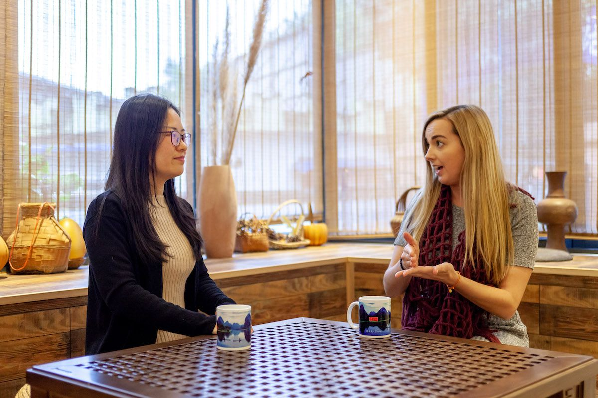 a girl with long blonde hair chats with a Chinese woman as the two sit at a table with two coffee mugs on it
