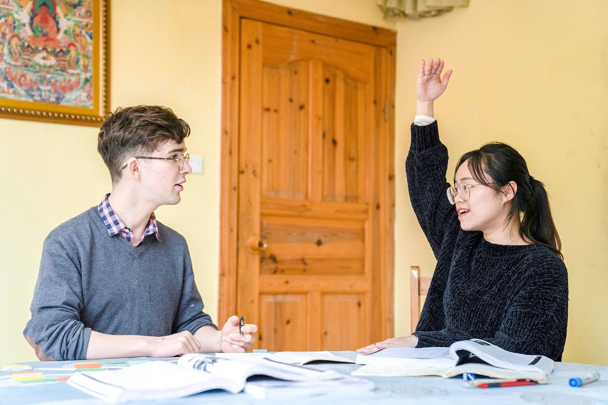 a western man sits at a table and looks at his Chinese teacher, who has her hand in the air