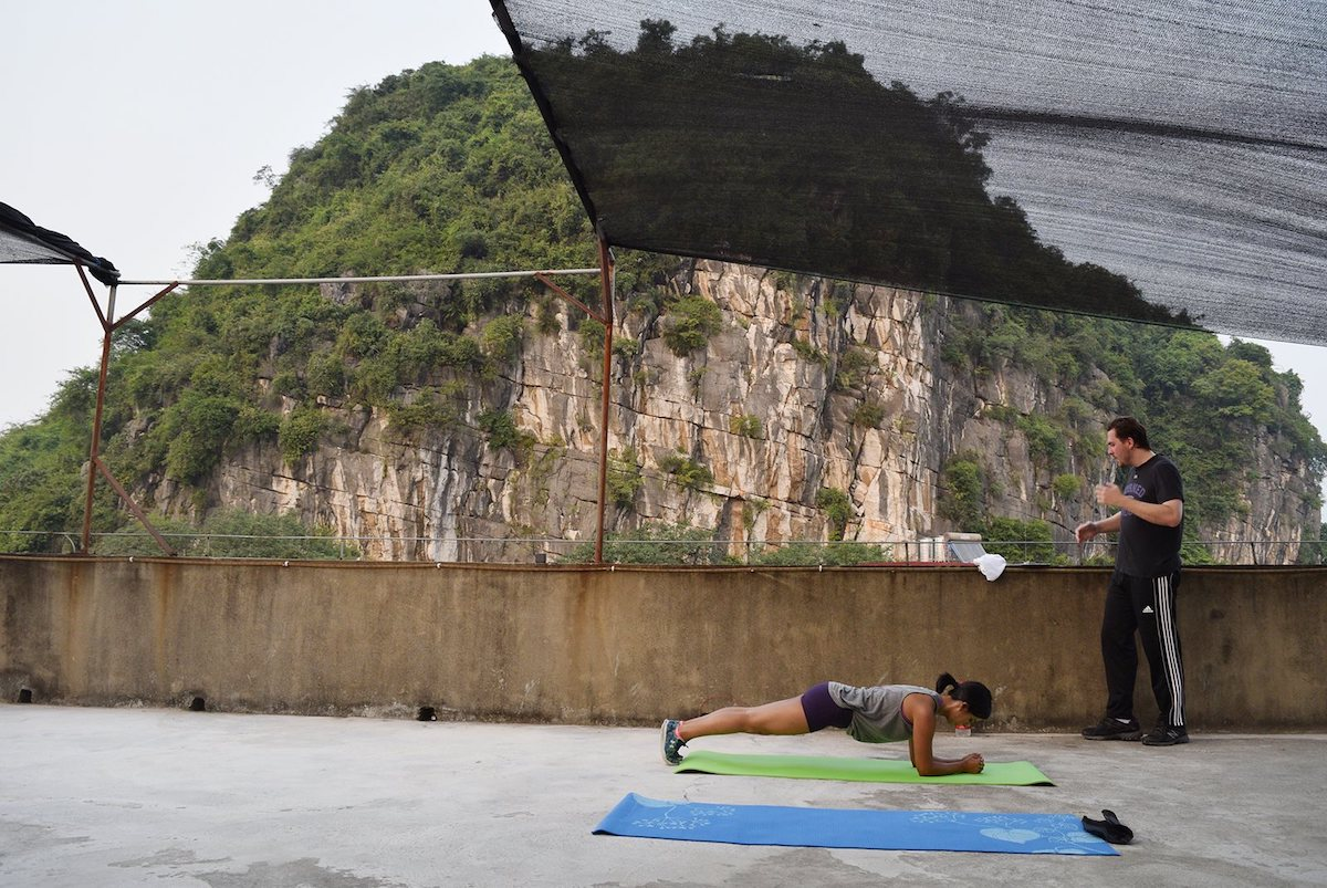 a woman exercises on a green mat on the rooftop of CLI while a man looks on