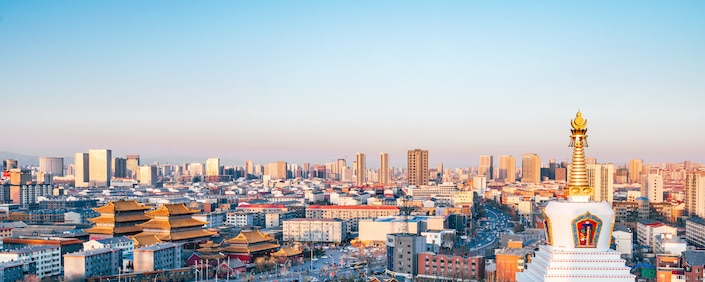 the skyline of a city in Inner Mongolia with a temple stupa in the foreground
