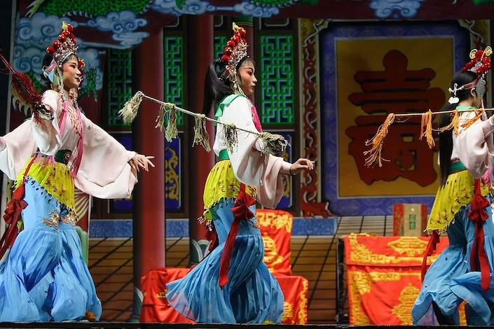 three Chinese opera performers in traditional dress performing a play