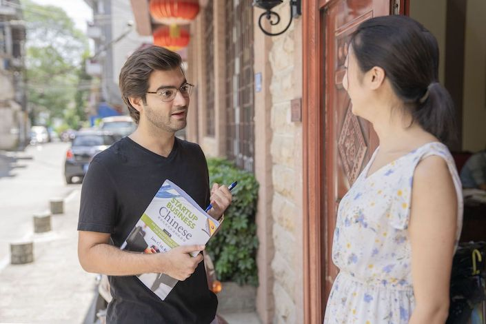a western man holding a startup business Chinese textbook speaks with a Chinese woman outside the CLI Center in Guilin, China