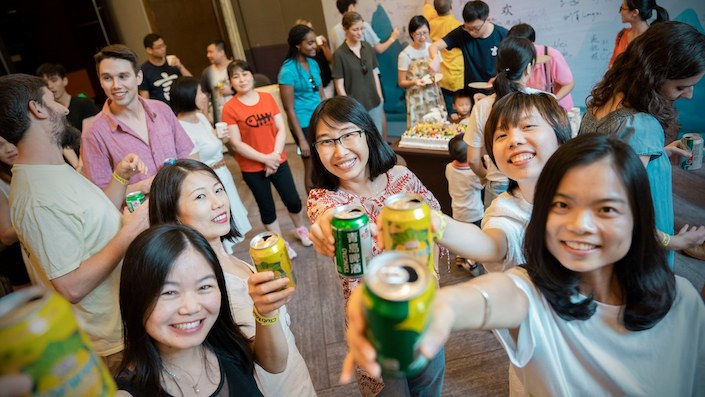 a group of young Chinese women toasting the camera with a canned beverage in their hands while multiple other people talk in the background