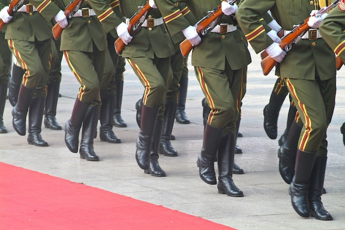 several rows of Chinese soldiers holding guns and wearing black boots while marching in unison, photographed from the waist down