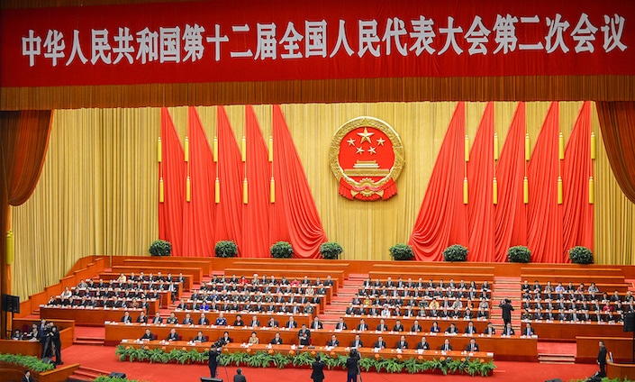 photo of a meeting of Chinese government officials with the seal of the People's Republic and two rows of red flags against a yellow wall behind them and a red banner with white Chinese characters above