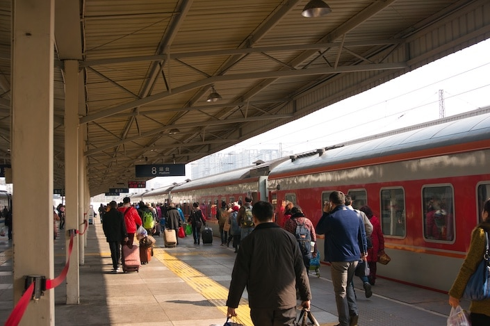 people carrying luggage walking on a covered platform next to an old-fashioned looking red train in China