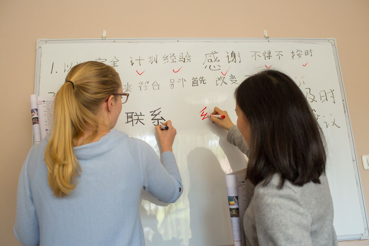 a blonde western woman with a pony tail and a Chinese teacher write Chinese characters on a whiteboard using markers