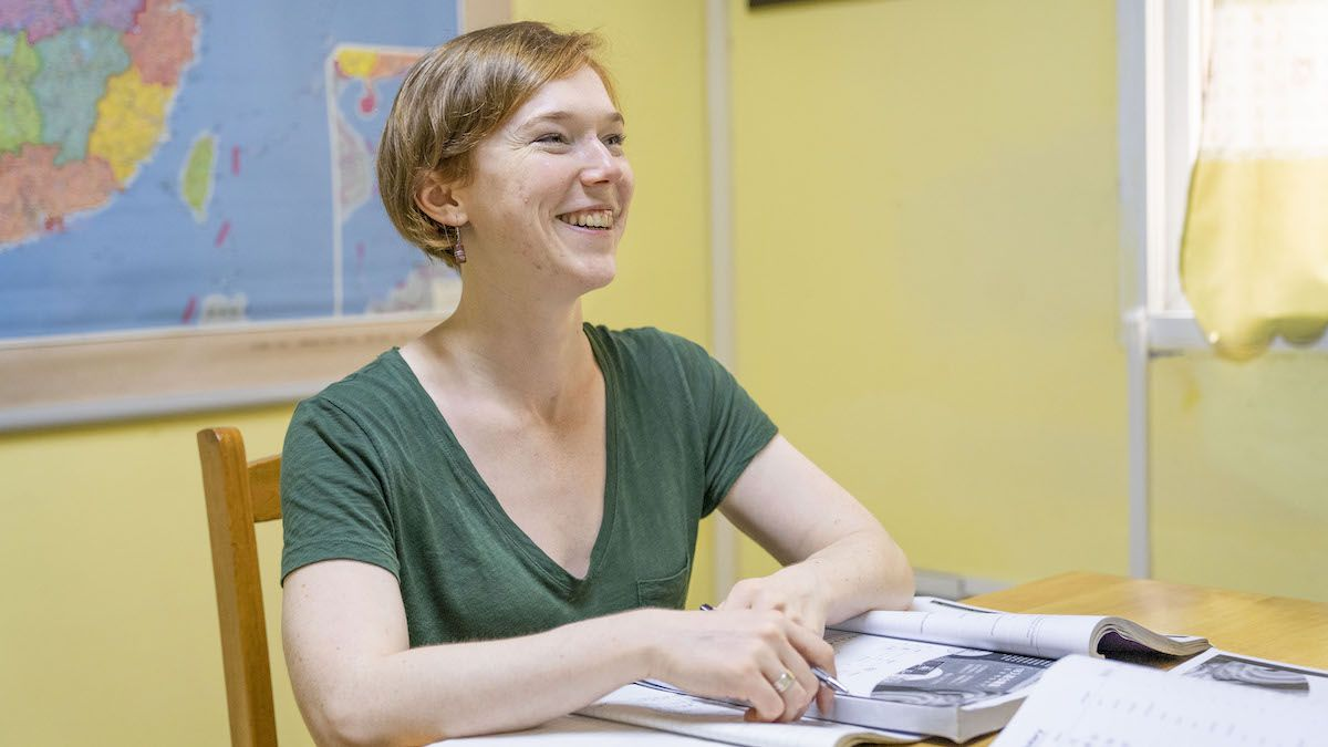 a western woman with red hair and a green T-shirt smiles as she sits at a table with a pen in her hand and a book open in front of her