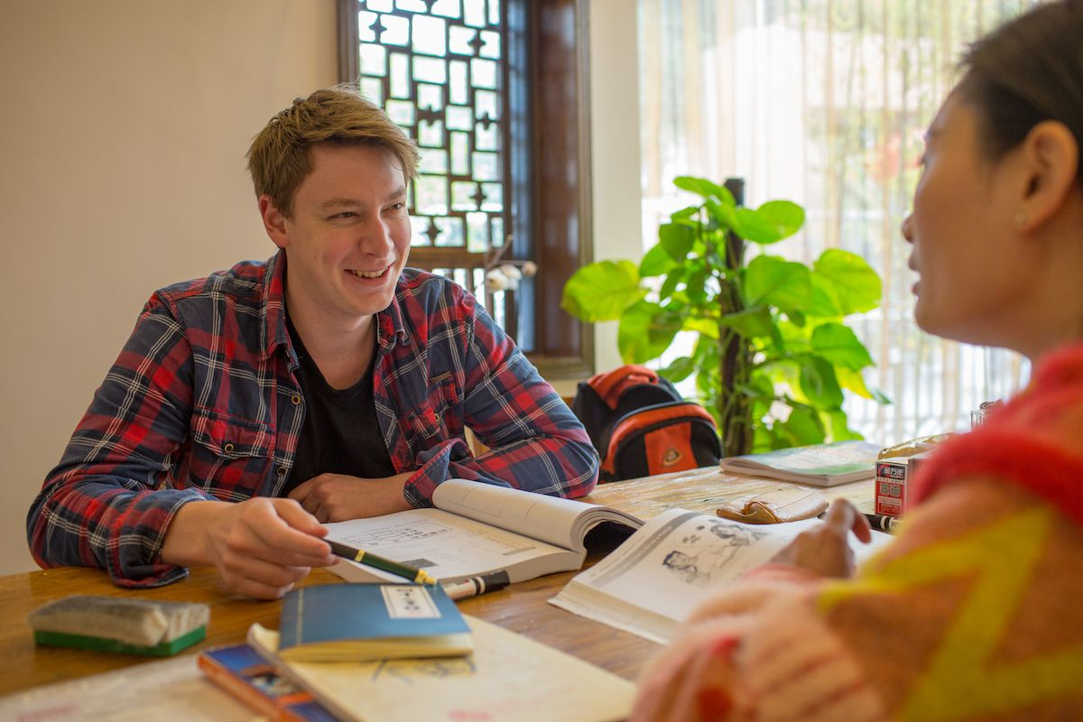 a western man with blonde hair wearing a plaid shirt sits at a table with a textbook open in front of him and smiles at his teacher
