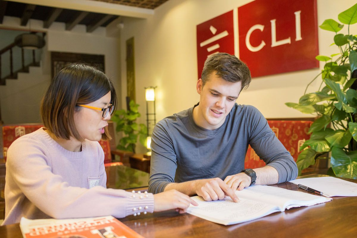 a western man and his Chinese teacher sit at a table below the CLI logo and point at a textbook open on the table in front of them