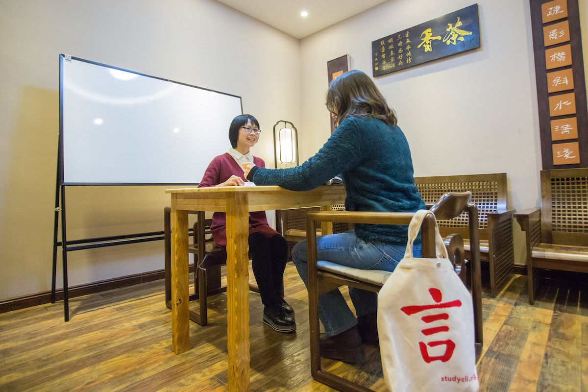 a Chinese teacher and student sit at a table with a whiteboard in the background at the CLI Center in Guilin, China