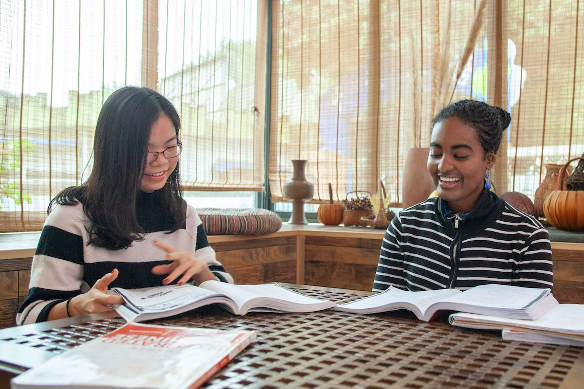 An African American woman and her Chinese teacher sit at a table with textbooks open in front of them in Guilin, China