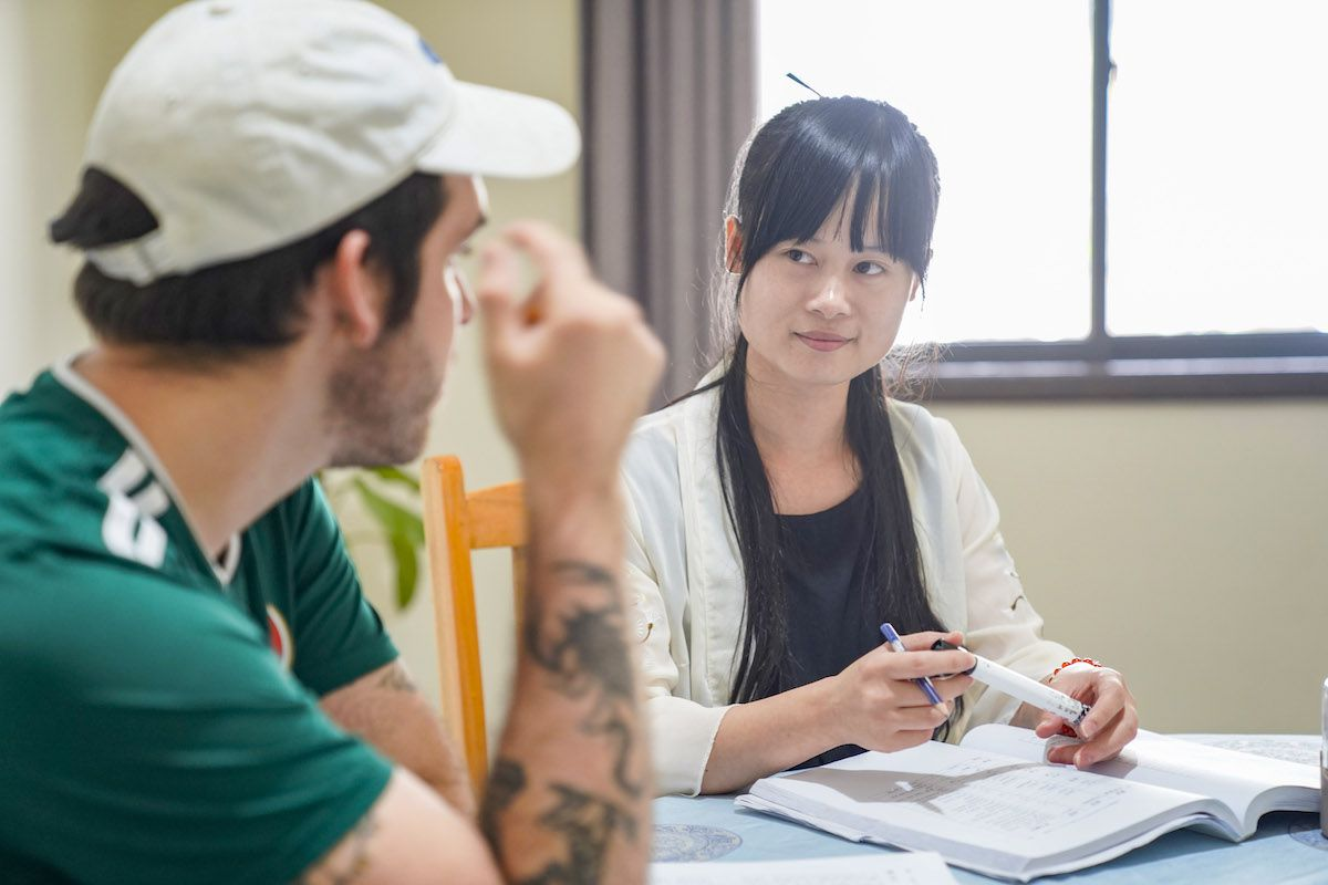 a western man with a tatoo on his arm looks at his Chinese teacher who is holding a marker as they have class