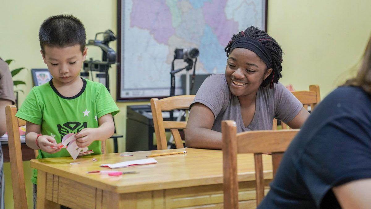 an African American woman sits at a table smiling at a small Chinese boy in a green shirt