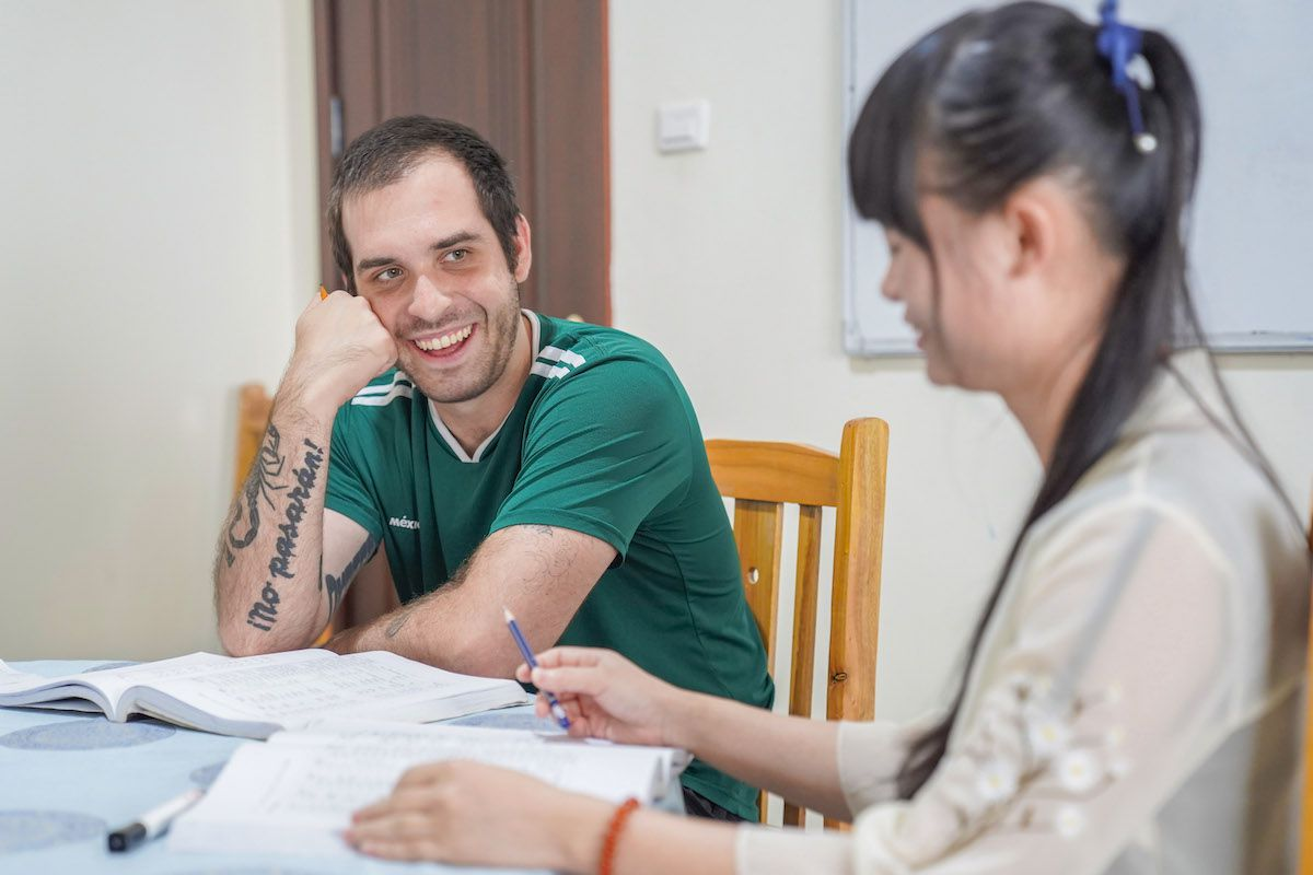 a western man with a tatoo on his arm and a textbook open on the table in front of him smiles at his Chinese teacher who sits in the foreground holding a pen