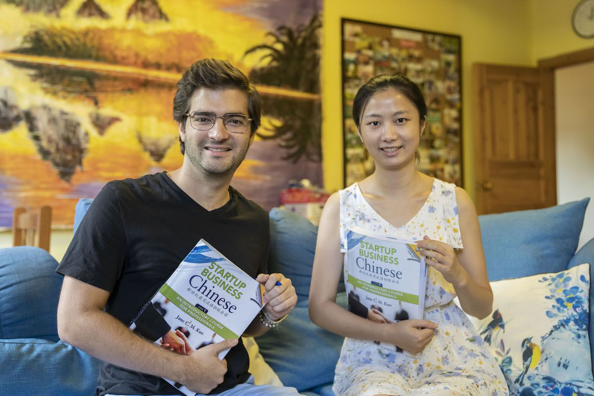 a western man with glasses holding a startup business Chinese textbook looks at the camera while sitting on a blue sofa next to a Chinese woman who is also holding a textbook