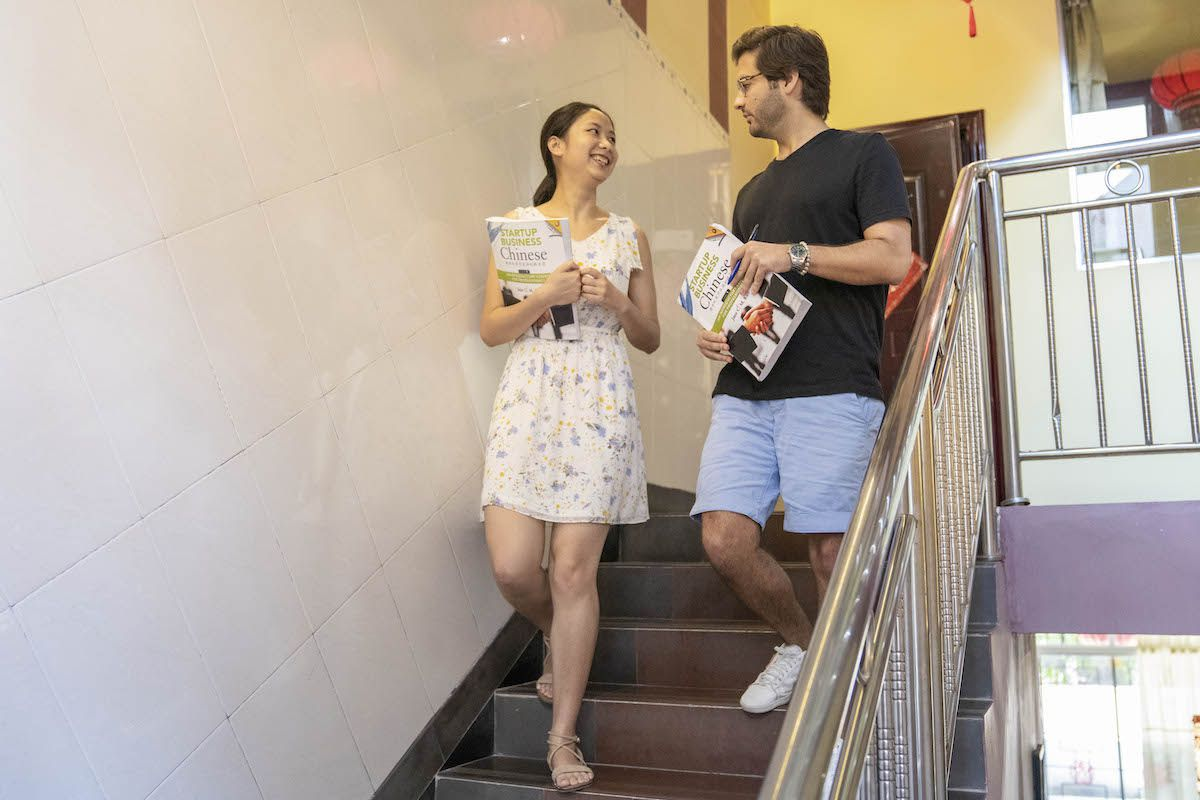 a western man holding a textbook walks down a flight of stairs while talking with a Chinese woman also holding a textbook