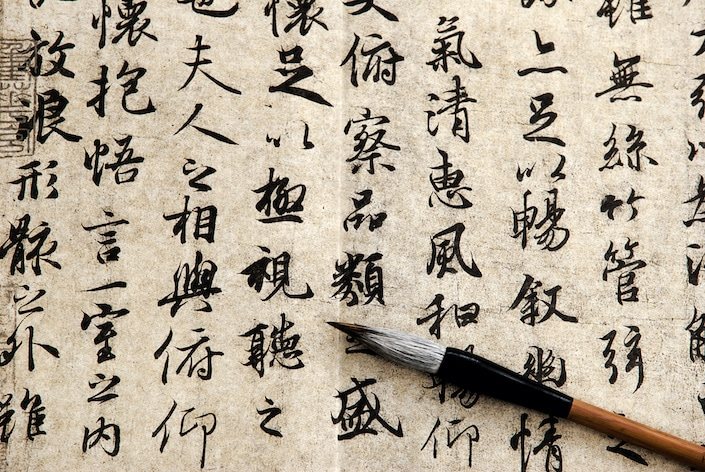 Chinese characters written on a piece of paper with a traditional Chinese calligraphy brush laying across it