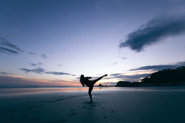 silhouette of a girl doing a kung fu kick on a beach at dusk