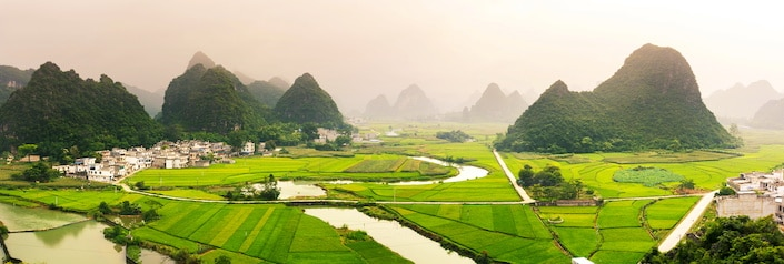 green fields in Guangxi Province, China with karst mountains scattered above them and small streams running through them