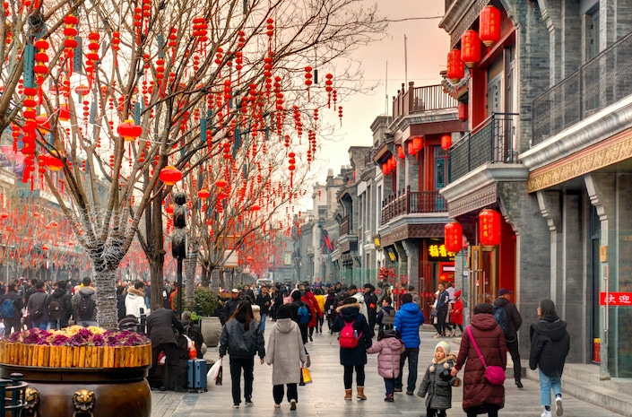 a winter street scene in China with red lanterns handing from trees and traditional Chinese buildings as people walk down the street