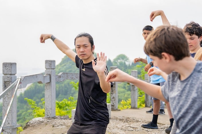 a Chinese man demonstrating a Chinese martial arts move to a group of American students who are trying to imitate him