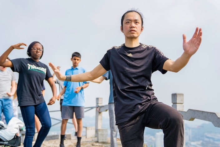 a Chinese martial arts instructor demonstrating a tai chi pose as students look on and copy him