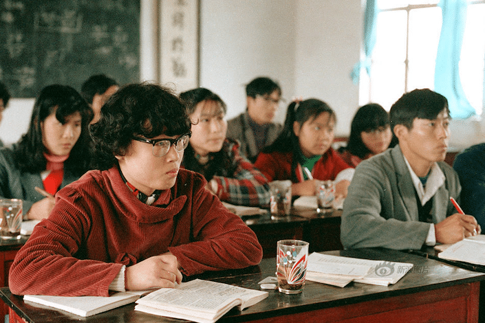a photo from the 1980's of Chinese university students sitting at desks in a classroom