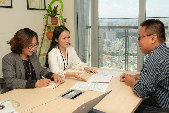 a Chinee man in a striped shirt sitting at a table across from two Chinese women in an office
