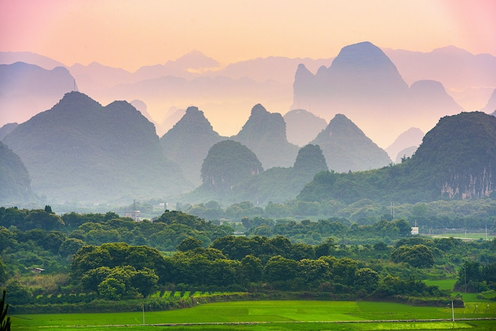 karst mountains rising above a green field and a stand of trees in Guilin, China