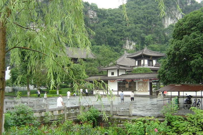 a white traditional Chinese building surrounded by a walkway and flanked by mountains in Guilin's Seven Star Park