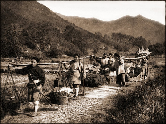 an old black and white photograph of farmers with shoulder poles walking along a path in the countryside with low mountains in the background