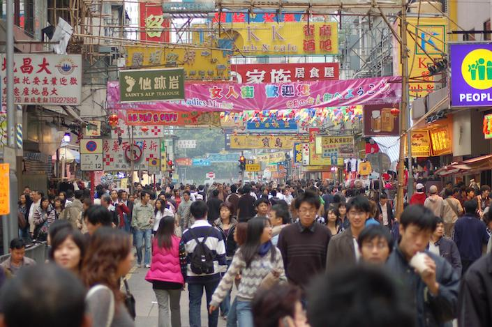 Hong Kong street scene showing a busy shopping street full of people with colorful banners strung across the street