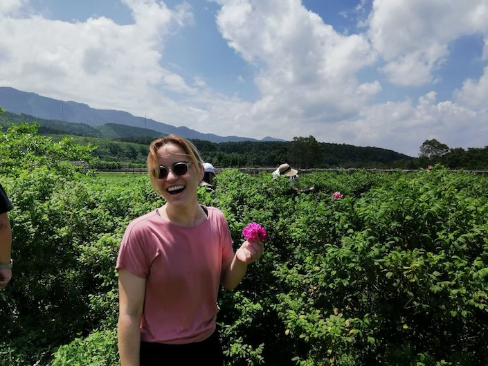 a woman wearing sunglasses and a pink T-shirt holding a flower in a field with mountains in the background on a sunny day