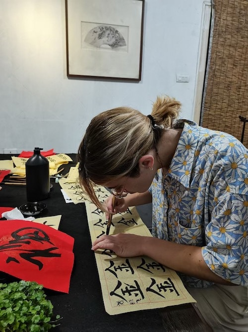 a woman with blonde highlights practicing Chinese calligraphy at CLI in Guilin, China