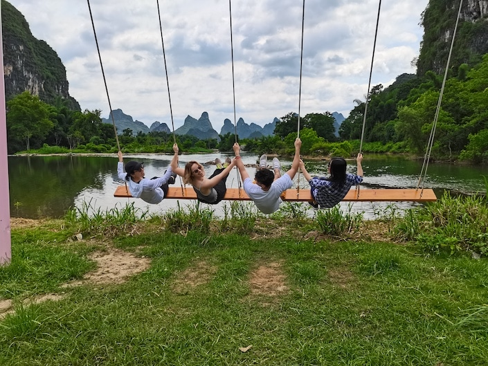 a group of four people sitting  on a five-person swing and swinging towards a lake with karst mountains in the background