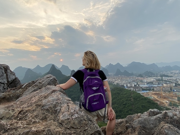 a blonde woman wearing a purple backpack sitting on top of a rock on a mountain overlooking karst peaks in Guilin, China