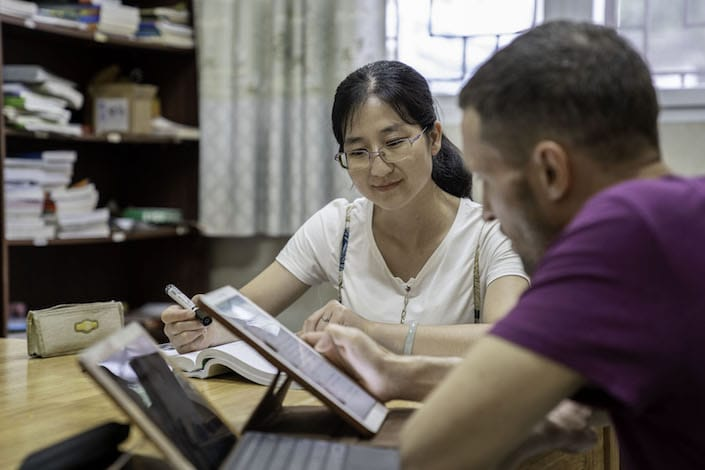 a female Chinese teacher looks on as a western man in a purple T-shirt uses a tablet to study Chinese