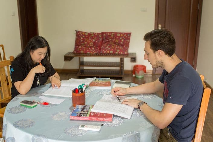 a western man and a Chinese woman looking at open textbooks and holding pens while sitting at a circular table