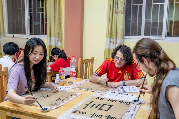 a Chinese woman and two western men with long hair sit at a table practicing Chinese calligraphy