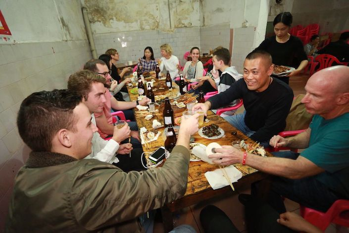 Chinese and western people sitting around a table having dinner in a traditional Chinese restaurant as a server bring more food in the background