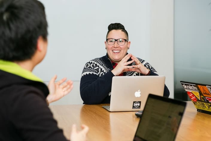 a woman with short hair sits at a table with an Apple laptop in front of her and smiles while listing to a man sitting across from her