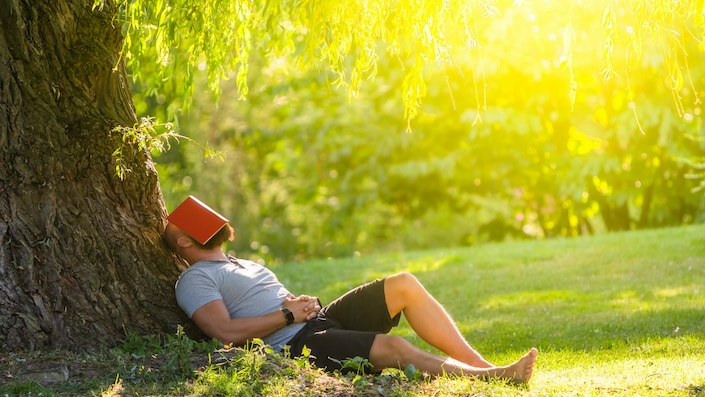 a man sitting in the grass outdoors while leaning against a tree with a red book covering his face