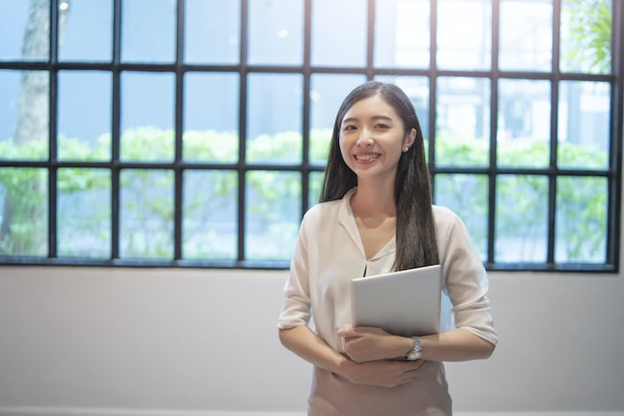 a smiling Chinese woman with long hair standing in front of a window holding some papers