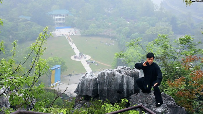 a Chinese man in black practicing tai chi on a mountain