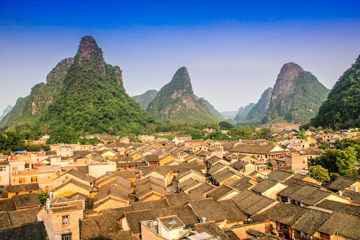 a village with traditional Chinese houses flanked by karst mountains in Guangxi Province, China