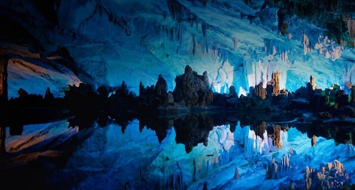 a view of rock formations illuminated with blue light in Seven Star Cave