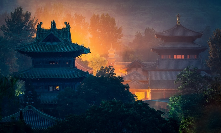 two buildings of the Shaolin Temple complex surrounded by trees and lit up with an orange glow
