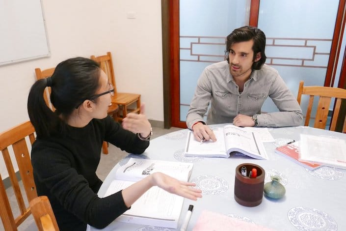 a western man with long hair having class with a female Chinese teacher while sitting around a circular table with several textbooks open on it
